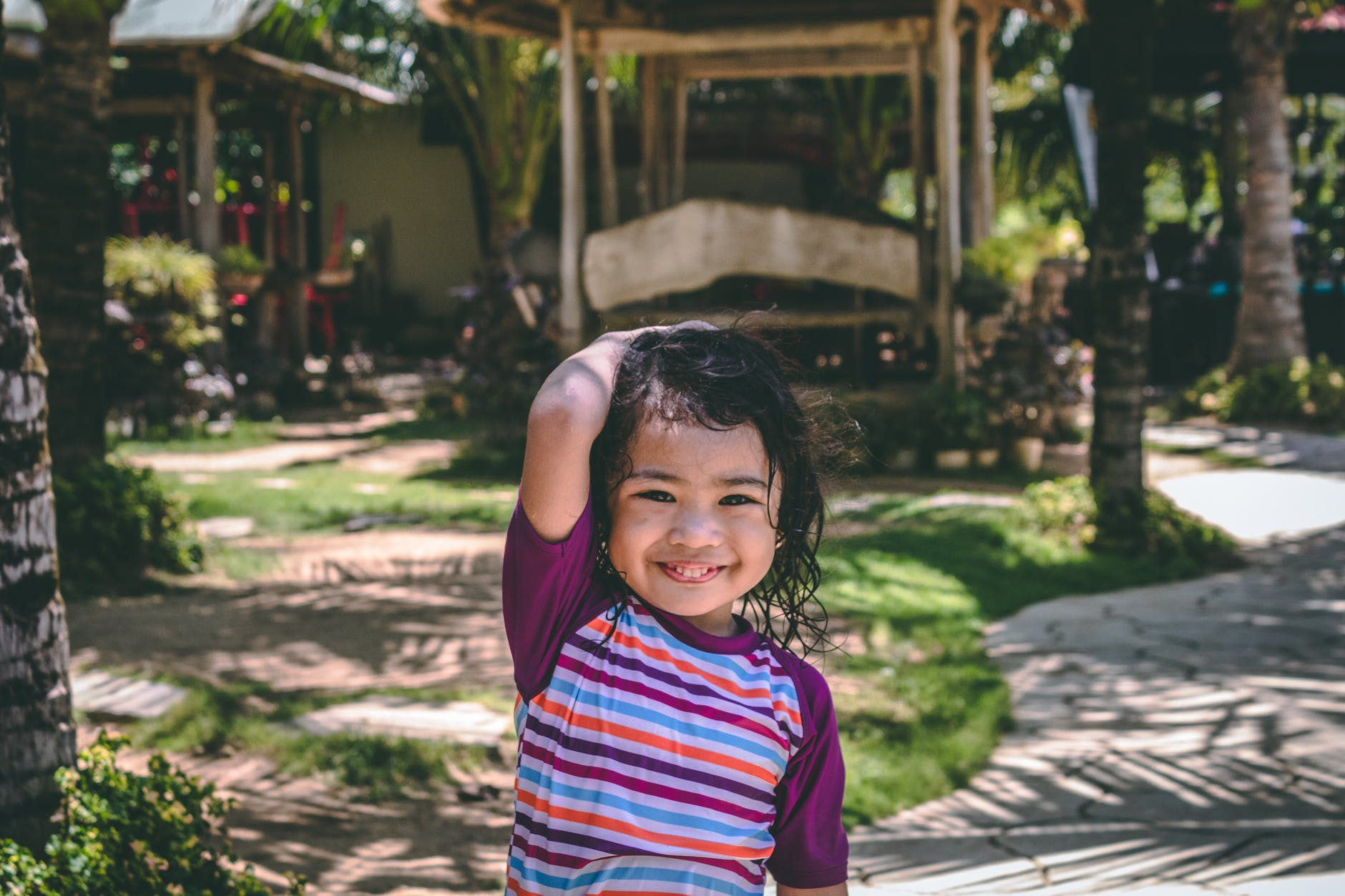 smiling girl wearing purple and multicolored striped top